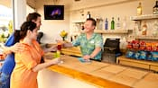 A Cast Member at a counter hands drinks to a couple at The Sand Bar snack shop