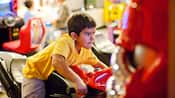 A boy sits on a motorcycle game inside an arcade