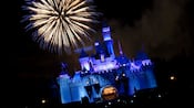Fireworks erupt over Sleeping Beauty Castle at night