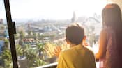 A girl and her younger brother look out a window onto Disney's California Adventure Park
