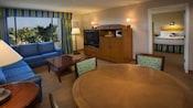 Dos sofás frente a una cómoda con televisión, microondas y una cubeta con hielo, al lado de un comedor