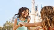 Soap bubbles float near 2 girls who hold hands and twirl, with Cinderella Castle in the background