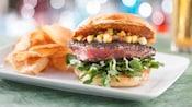 Hamburger de thonAhi, avec une salsa au concombre et à la mangue, du cresson, de l'aïoli à l'ail et des croustilles de pommes de terre