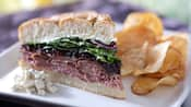 Beef and blue sandwich with potato chips on plate