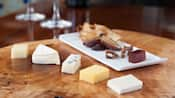 Cheese slices on table with appetizers on a plate in background