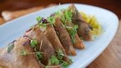 Crispy beef 'bobotie' rolls on plate