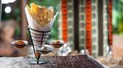 Support métallique en forme de cône contenant des tranches croustillantes de pains africains et 3trempettes et sauces