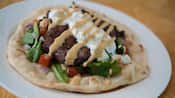 Open-faced grilled lamb kefta sandwich on naan with tamarind glaze