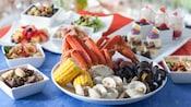 Assiette de pattes de crabe, de palourdes, de moules, épi de maïs et pommes de terre, à côté d'autres assiettes de nourriture