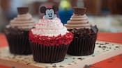 3 cupcakes de chocolate, um deles com cobertura branca e granulado vermelho coberto com uma imagem do Mickey Mouse