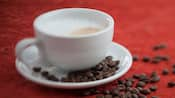 Cup of cappuccino with coffee beans scattered in saucer and on table