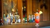 Southern Belle em um copo alto de coquetel com garrafas de bebidas alcoólicas ao fundo