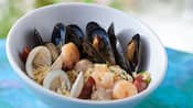 Bowl of steamed clams, shrimp and mussels with sausage and rice