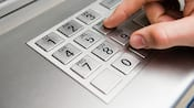 Primer plano de los dedos de un hombre presionando los números en el teclado de un cajero automático