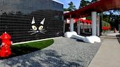 Un pared exterior negra brillante adornada con la cara de un gato al lado de un área de grava con un hueso gigante de perro y un área de césped con una boca contra incendios