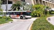 Um ônibus branco entrando em uma estrada, saindo do Disney's Contemporary Resort