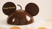 A Chocolate Cake Designed To Resemble Mickey Mouse Inscribed With The Message Happy Birthday