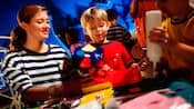 A Cast Member helps a boy with his arts and crafts project