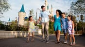A smiling couple and their 3 young kids hold hands while crossing the bridge near Cinderella Castle