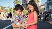 Un hermano y una hermana sostienen una estatuilla de Tinker Bell de pie en Disney's Hollywood Studios