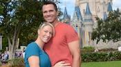 A woman hugs her husband outside Cinderella Castle in Fantasyland