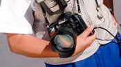 Una cámara con una gran lente, colgada del brazo de un fotógrafo de Disney PhotoPass