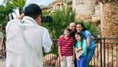 Una madre, un padre, una hija y un hijo posan para una foto tomada por un fotógrafo de Disney PhotoPass