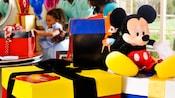 Coloridas cajas de regalo envueltas con un gran Mickey Mouse de peluche sentado encima