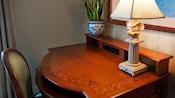 Uma mesa em madeira com um vaso de planta, um abajur do Mickey Mouse e uma cadeira