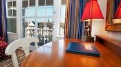 Un bureau en bois, avec une lampe MickeyMouse, un guide des visiteurs et une chaise en bois blanche se trouvent à proximité de portes-fenêtres coulissantes donnant sur un balcon