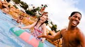 Hóspedes em trajes de banho aproveitam a água da piscina na altura da cintura