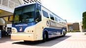 """Vista frontal de un autobús azul y blanco llamado """"Disney's Magical Express"""""""