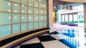 Plancher à carreaux noir et blanc avec un quadrillage incurvé de fenêtres givrées dans un hall d'entrée