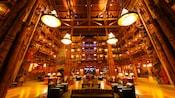 Áreas de estar com poltronas estofadas escuras e sofás listrados dentro do saguão do The Villas at Disney's Wilderness Lodge
