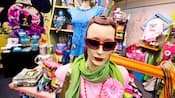 Mannequins dans un magasin portant des lunettes de soleil, écharpes, colliers et t-shirts