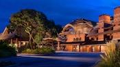 Un área iluminada de servicio de estacionamiento valet revela el exterior de estilo safari de Disney's Animal Kingdom Lodge