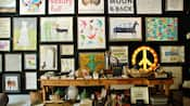 A wall display of an illuminated marquee peace sign and framed prints in various sizes and a wooden console containing assorted small gift items inside the Sugarboo boutique