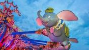 A Dumbo gondola flies high at Dumbo the Flying Elephant at Magic Kingdom park