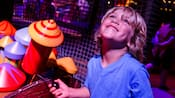 A boy looks up with delight while in the wait area for Dumbo the Flying Elephant attraction
