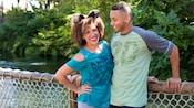 2 Visitantes em uma ponte do Disney's Animal Kingdom Theme Park usando roupas e acessórios do 20.ºaniversário