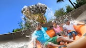 A father, son and daughter get splashed while riding on a family raft at Miss Adventure Falls