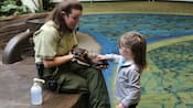 A woman holds a ferret while a little girl pets it