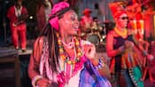 Two female performers wearing festive African style dresses and adornments dance joyously on stage as male musicians play instruments in the background