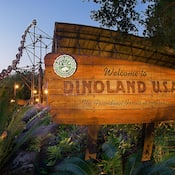 """A large dinosaur bone display next to a wooden sign that reads """"Welcome to Dinoland U.S.A."""""""