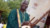 The street musician Kora Tinga Tinga strolls through Harambe Village playing the kora, a traditional African harp