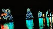Una serpiente marina hecha de luces coloridas parece elevarse sobre las aguas de Seven Seas Lagoon