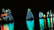 A sea-serpent realized in colorful lights seems to be rising from the waters of Seven Seas Lagoon