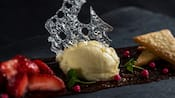 Ice cream garnished with a slice of crystalized sugar next to strawberries and short cake