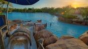 The sun peeks over trees, illuminating Bay Slides at Disney's Typhoon Lagoon water park