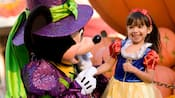 A young female Guest dressed as Snow White smiling while she meets a Halloween-themed Mickey Mouse